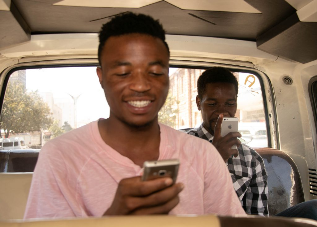 ZImbabwean men using cellphones in Minibus Kombi